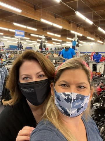 Two women with masks on take a selfie during a clothing drive for local schoolchildren.